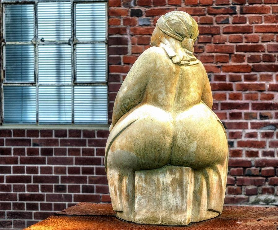 Rauchstopp Gewichtszunahme - Dicke Frau sitzt auf einem Sockel